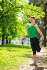 Young sports woman stretching and exercising outdoors