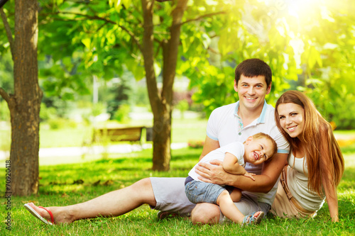 Happy young family having fun in the green summer park outdoors - 70920418