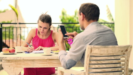 Young couple counting bills, payments with smartphone on terrace