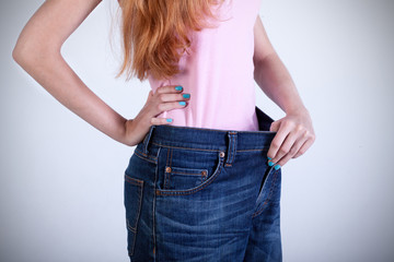Woman trying on her old big jeans