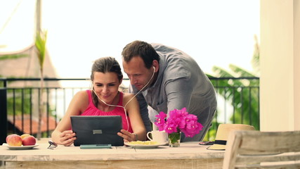 Young couple watching movie on tablet computer on terrace