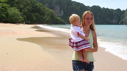 child in embroidery on the beach with mother on islands