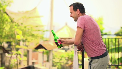 Young man drinking beer, standing on terrace