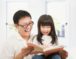 smiling  father and her daughter reading a book at home