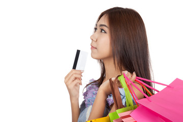 Asian woman touch credit card to chin think what to buy