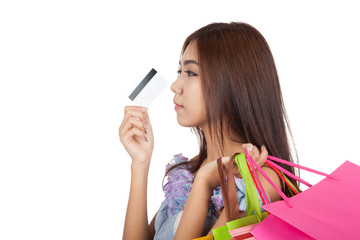 Happy Asian woman touch credit card to nose think what to buy