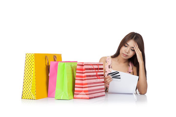 Beautiful Asian woman headache with a credit card statement and