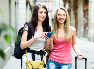 Two nice girls finding path with GPS navigator