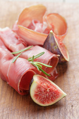 dried jamon slices with figs on wood table