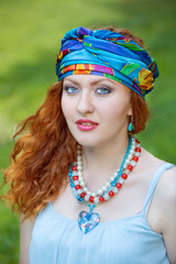 red haired girl wearing a turban in the park