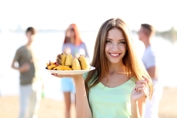 Young woman with grilled vegetables on plate on rest, outdoors