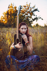 Fashion portrait of young hippie woman with guitar