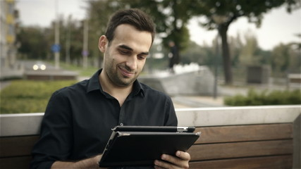 Happy businessman using digital tablet at park