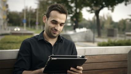 Happy businessman using digital tablet at park