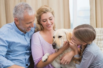 Parents and daughter with pet labrador