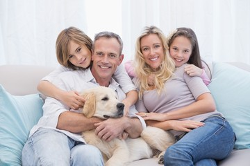 Cute family relaxing together on the couch with their dog