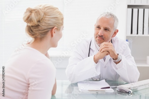 Patient consulting a happy doctor - 70929040