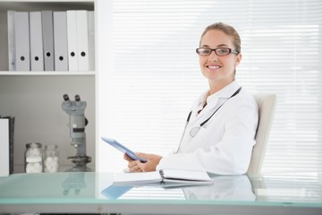 Smiling doctor using her tablet