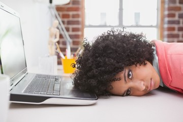 Casual businesswoman resting head on desk