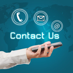 Business hand showing smartphone with  word contact us and icon