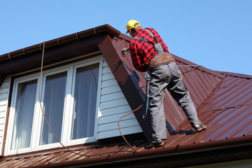 roofer builder worker spraying paint on metal sheet roof