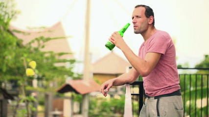 Young man drinking beer and smoking cigarette on terrace