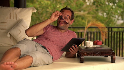 Happy, cheerful man with tablet computer relaxing on gazebo bed