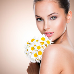 Face of young beautiful woman with posy flowers