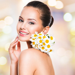 Smiling young beautiful woman holds a posy flowers