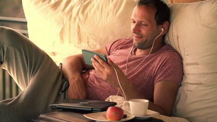 Young man watching movie on smartphone, lying on gazebo bed
