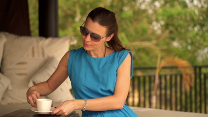 Pretty woman drinking coffee while sitting on gazebo bed