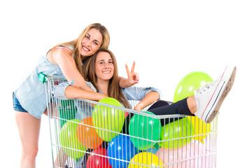 blonde girls inside supermarket cart
