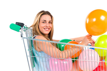 Blonde pretty girl inside supermarket cart