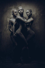 Naked women painted in grey color posing over grey wall