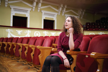 Beautiful woman sit in empty auditorium and looks at stage