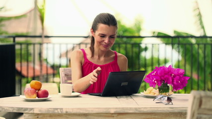 Woman with laptop computer having coffee break on terrace