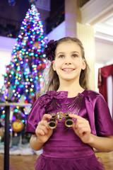 Girl with binocular stands near christmas tree in big theater