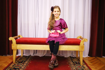 Beautiful girl in dress sits on soft bench near curtains