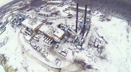 Industrial area with machines and crane at winter day.