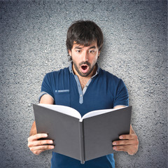 Man reading a book over textured background