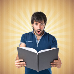 Man reading a book over pop background
