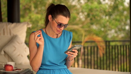 Young woman using smartphone, eating cookie on gazebo bed