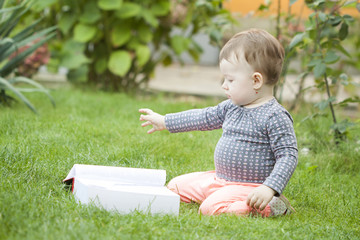 Baby girl looking at a book in the park