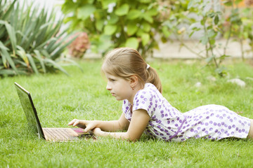 Girl using laptop in the meadow