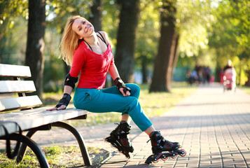 Beautiful young woman in roller skates sitting on park bench