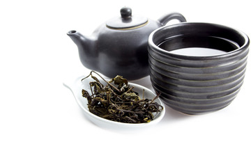 a cup of black tea with teapot on white background