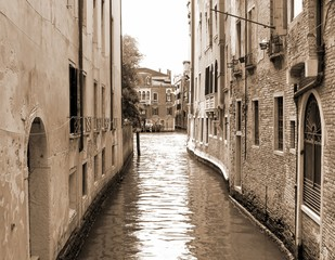 narrow navigable canal in Venice in Italy sepia