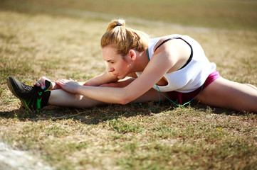 Young woman doing stretching exercise, workout on grass field