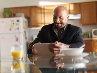 happy african guy with tablet in kitchen with breakfast