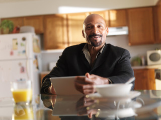 african american man with tablet at breakfast in kitchen